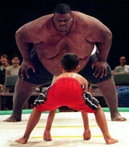 Photo of huge Sumo Wrestler facing off against a small child